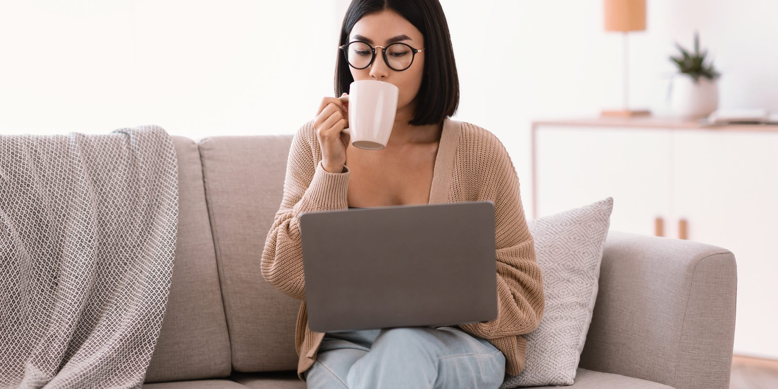 Morning Concept. Portrait of asian female freelancer drinking coffee at home and using laptop, working online, copy space. Lady in glasses holding cup, sitting on sofa at home office
